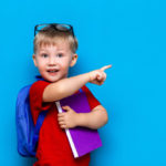 back-school-first-grade-junior-lifestyle-small-boy-red-t-shirt-close-up-studio-photo-portrait-smiling-boy-glasses-with-schoolbag-book-indicating-with-his-finger_93267-788